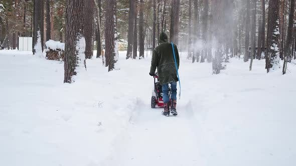Thumbnail for Man Cleans Park Road Walking with Snow Blower and Shovel
