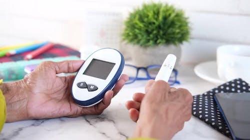 Senior Women Hand Holding Diabetic Measure Glucose on Table