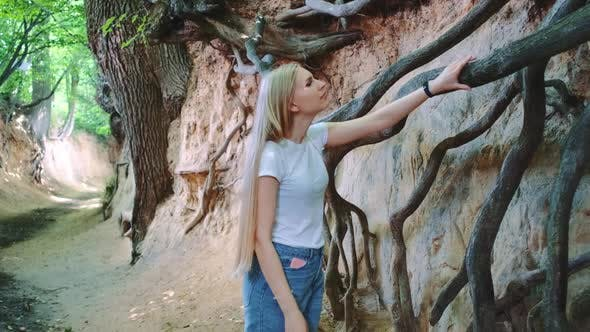 Young Blonde Woman Looking on Exposed Tree Roots in Natural Loess Ravine