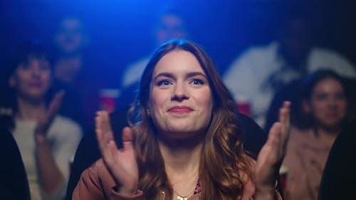 Amazed Woman Applauding at Movie Premiere. Smiling Girl Enjoying Film in Cinema.