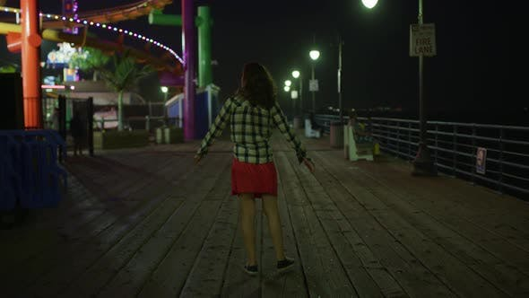 Thumbnail for Young woman walking by the Pacific Park, at night