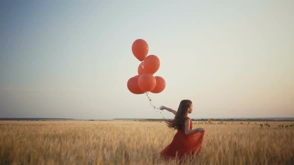 Thumbnail for Happy Young Girl with Balloons Running in the Wheat Field at Sunset.  Video.