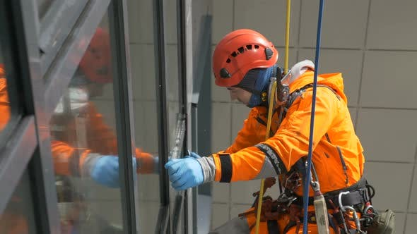 Industrial Climber in Orange Overalls and Helmet Washes Windows on Tall Building Outside.