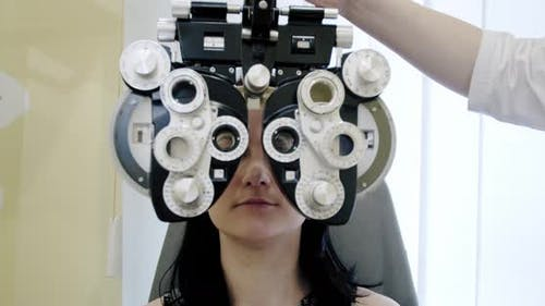 Eyesight Measurement To Young Woman with Optical Phoropter. Woman Doing Eye Test Slow Motion