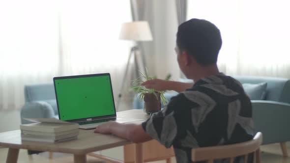 Asia Boy sitzt an seinem Schreibtisch und lernt online auf einem Laptop mit grünem Mock-up-Bildschirm zu Hause