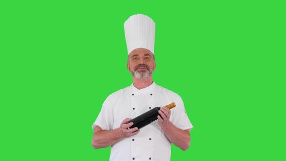Senior Chef Holding a Bottle of Perfect Red Wine and Smiling To Camera on a Green Screen Chroma Key