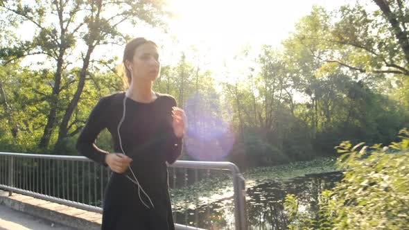 Thumbnail for Woman Jogging in Park Outdoors. Fitness Girl Runs in the Morning During the Sunrise