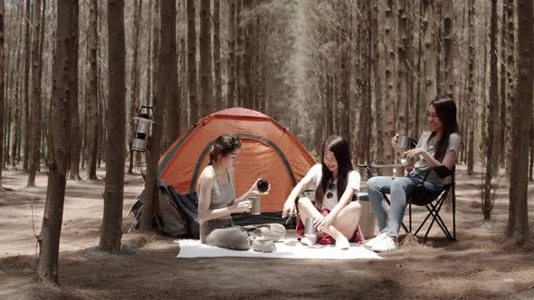 Asian friends camping or picnic together in forest, teenager female enjoy talking in front of tent