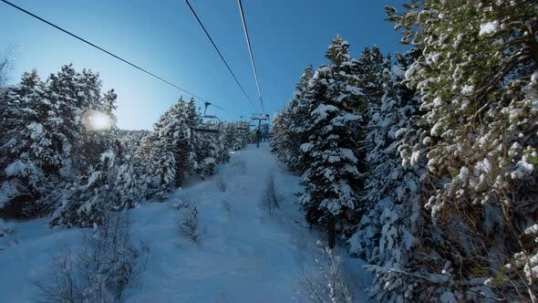Thumbnail for Riding Ski Chair Lift Through Snowy Forest