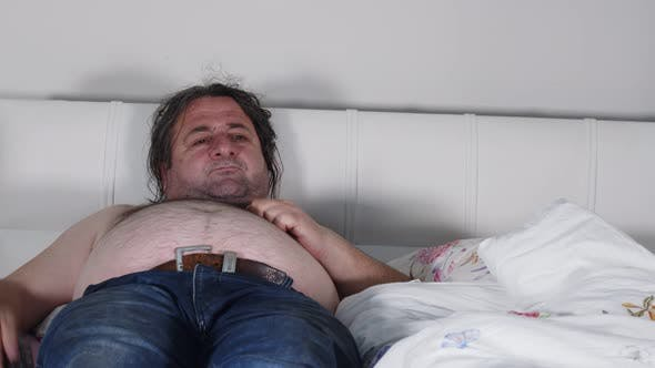 Fat Man Eating In Bed Watching Television 5