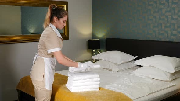 Cleaning Service. Close-up of Maid Hands Putting One White Towel on Top of Stack with Fresh Bath