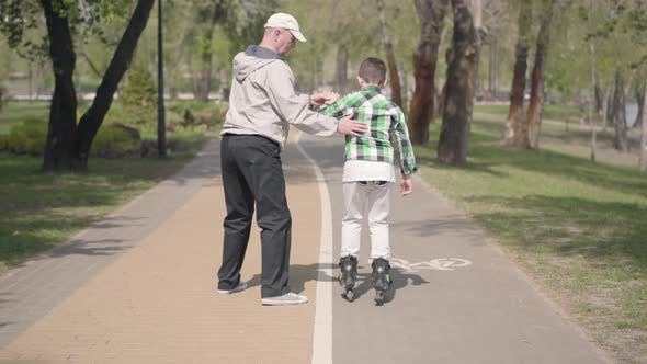 Thumbnail for Grandfather Teaches His Grandson To Roller Skate in the Park