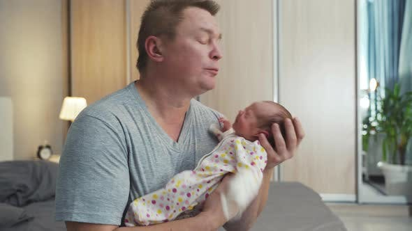 Thumbnail for Father Holds Hands His Newborn Baby