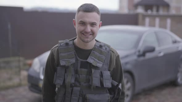 Thumbnail for The Young Happy Man in Military Closes in the Bulletproof Vest Standing in Front of the Car