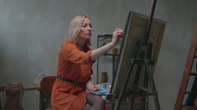 Artist Painting Picture on Canvas with Oil Paints in Workshop