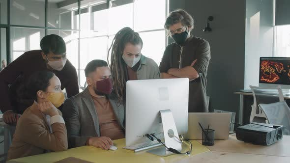 Team of Businesspeople in Face Masks Brainstorming