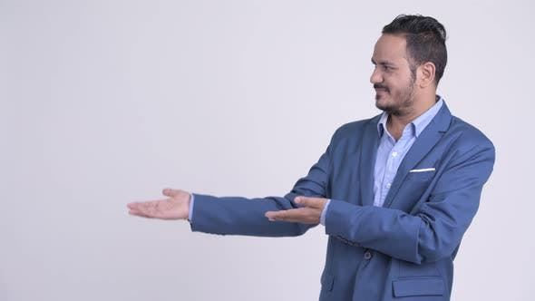 Thumbnail for Happy Bearded Indian Businessman Showing Something