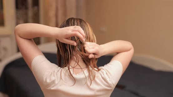 Woman Applying Cream on Her Hair for Restore