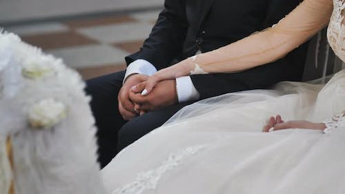 The Hands of the Newlyweds Are Joined Together at a Catholic Wedding Ceremony in the Church.