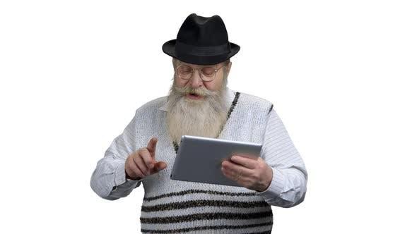 Aged Man in Eyeglasses Using Digital Tablet