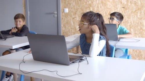 Schüler sitzen mit Laptops an Schreibtischen