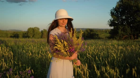 Thumbnail for Young Woman Walking With Bouquet of Field Flowers