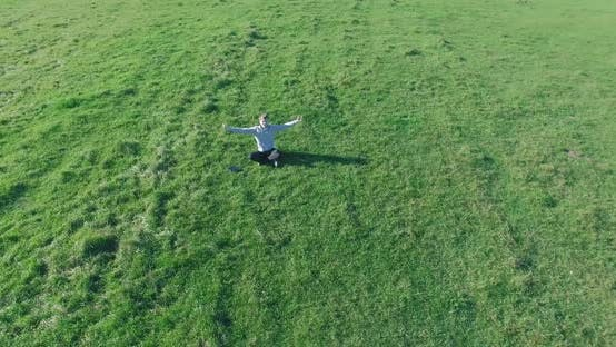 Thumbnail for Low Orbital Flight Around Man on Green Grass with Notebook Pad at Yellow Rural Field