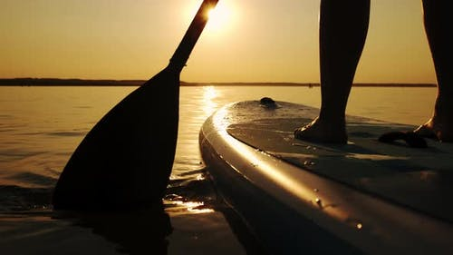 Close Up of Woman Standing Firmly on Inflatable SUP Board and Paddling Through Shining Water Surface