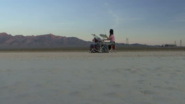 Female playing drums in desert