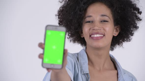 Cover Image for Face of Young Happy African Woman Showing Phone