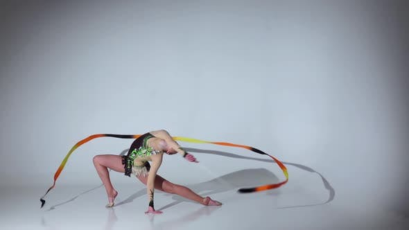 Thumbnail for Rhythmic Gymnast Sit on One Leg on the String. White Background. Slow Motion