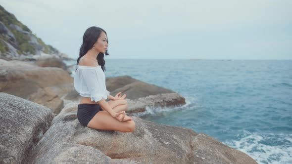 Thumbnail for Woman Meditating and Smiling By the Ocean
