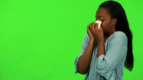 Thumbnail for A Young Black Woman Blows Her Nose Into a Paper Tissue - Green Screen Studio