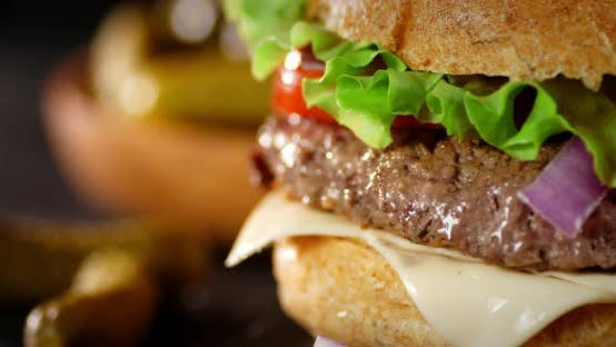 A Delicious Burger with Beef Patty Rotates on the Table.