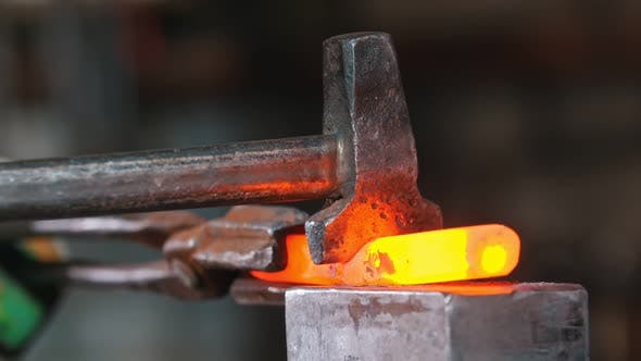 Cover Image for Blacksmith Cutting the Piece of Incandescent Metal with an Axe and Industrial Forging Pressure
