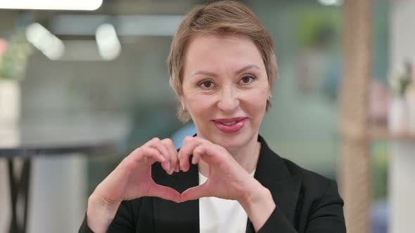 Old Businesswoman Showing Heart Sign with Hand
