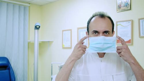 Front View Portrait of a Doctor Putting on a Surgical Mask, Slow Motion. Healthcare Workers in the