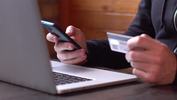 Thumbnail for Businessman in a Black Hoodie Making Online Payment with Credit Card and Smartphone, Online Shopping