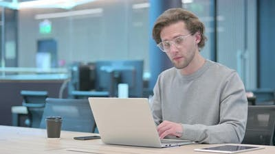 Young Businessman with Laptop Smiling at Camera