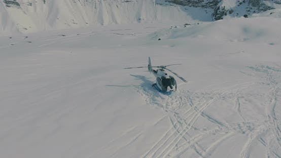 Thumbnail for Aerial view, around Heliskiing helicopter and group of skiers, snowboarders in the winter mountains