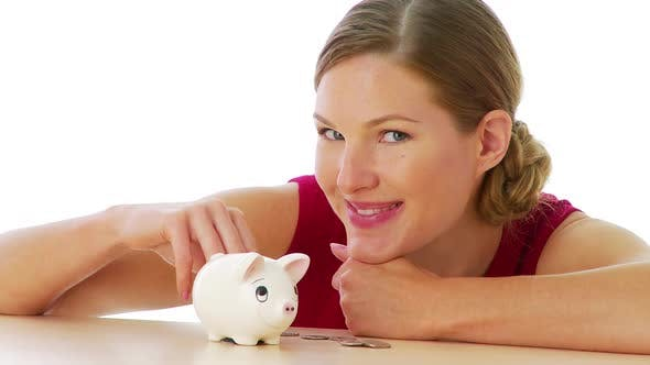 Thumbnail for Woman putting money in piggy bank