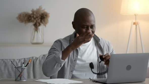 Black Man Taking Off Headset Tired After Work At Home