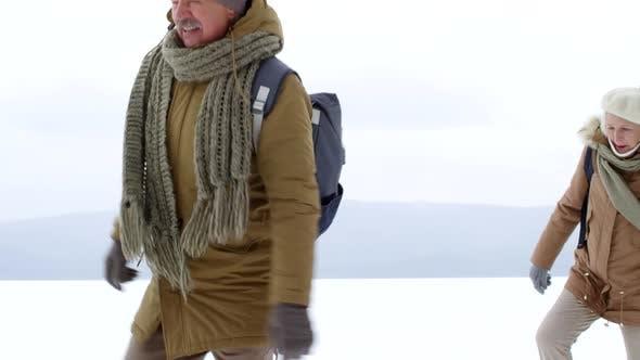 Thumbnail for Adventurous Elderly Couple Waddling in Snow over Frozen Lake