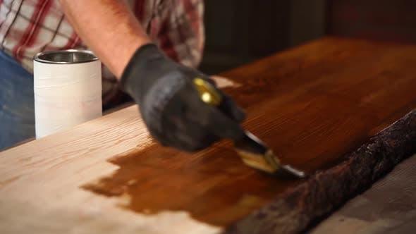 Thumbnail for Der Mann wendet braunen Lack auf einer Oberfläche von Holzbrett an, Malerei