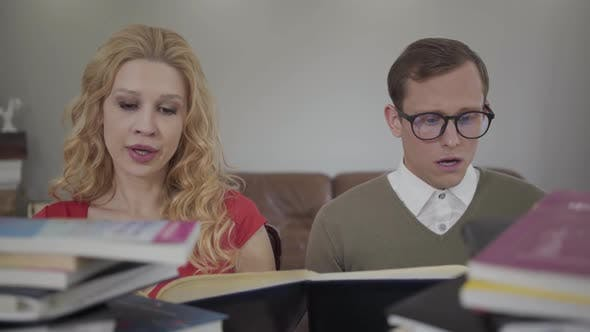 Thumbnail for Beautiful Blond Woman and Modestly Dressed Man Sitting at the Table Working