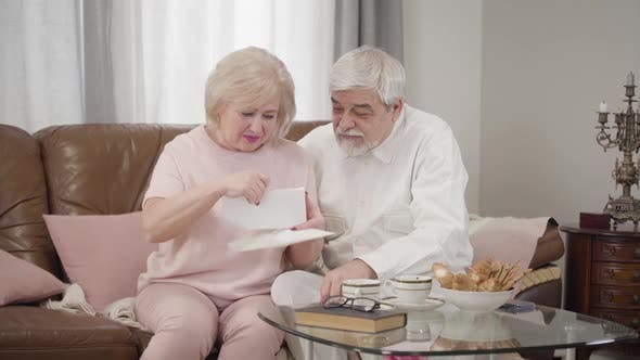 Thumbnail for Mature Blond Caucasian Woman Opening Envelope and Reading Letter with Husband, Retired Married Man