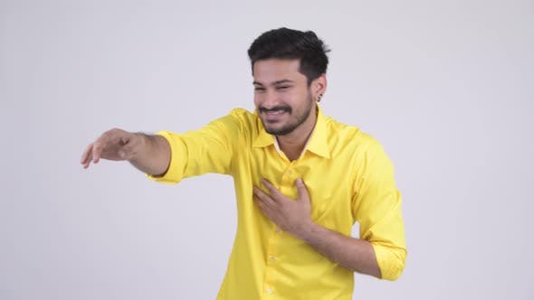 Thumbnail for Young Happy Bearded Indian Businessman Laughing While Pointing Finger
