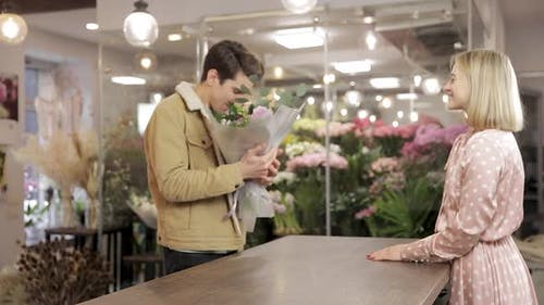 Handsome Young Man Leaves The Flowers Store With Bouquet
