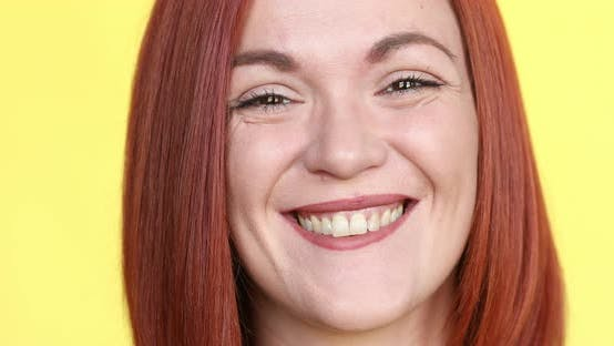 Thumbnail for Positive Red Haired Woman Smiling at Camera, Posing on Yellow Background