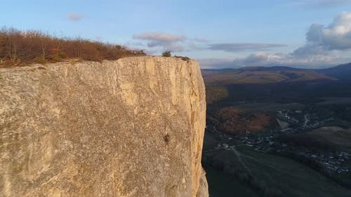 Rocky cliff on background horizon of mountain
